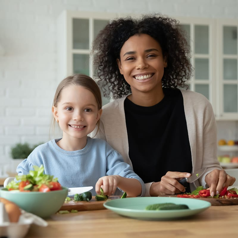 Portrait of smiling African American mom and little Caucasian daughter look at camera cooking in kitchen together, happy biracial mother and small girl child have fun preparing healthy food at home
