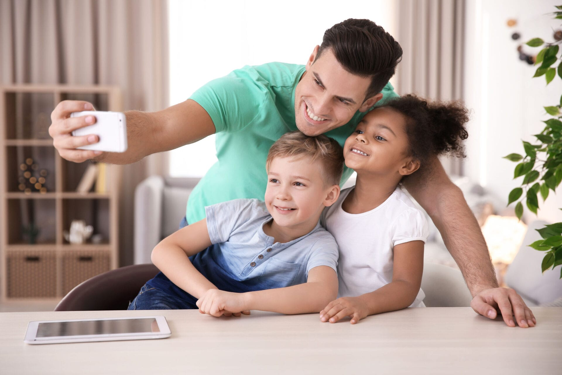 Young man taking selfie with little kids indoors. Child adoption